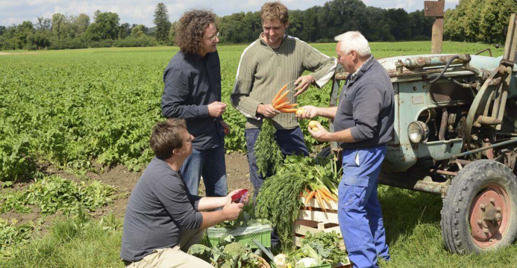 JooTi Mitarbeiter mit Biobauer auf Feld