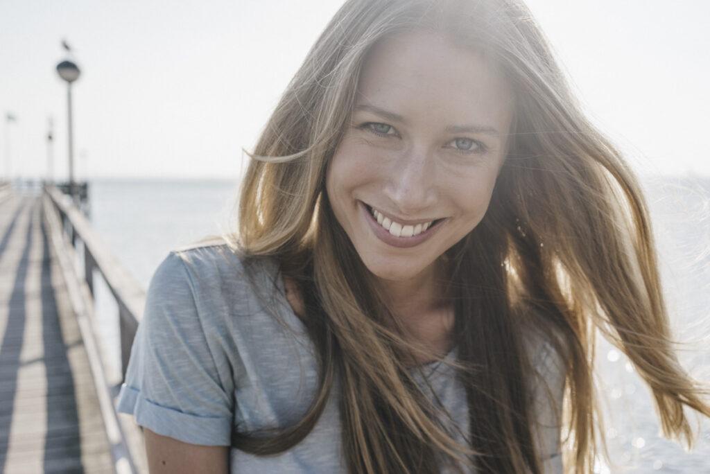Frau mit strahlendem Lächeln an Steeg