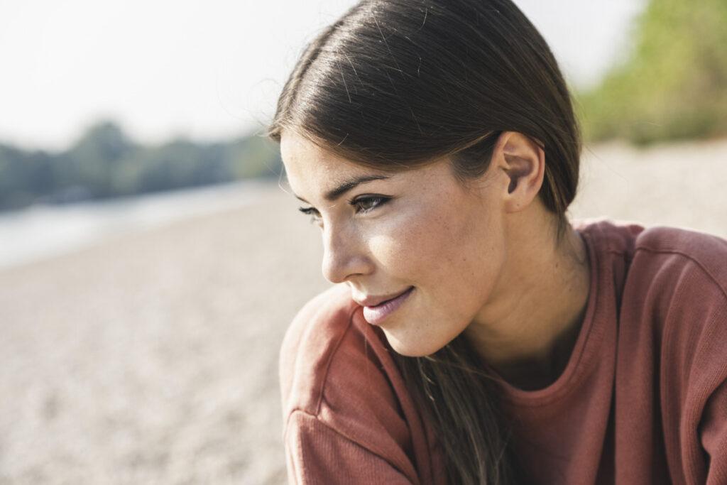 Frau mit klarer Haut schaut in die Ferne