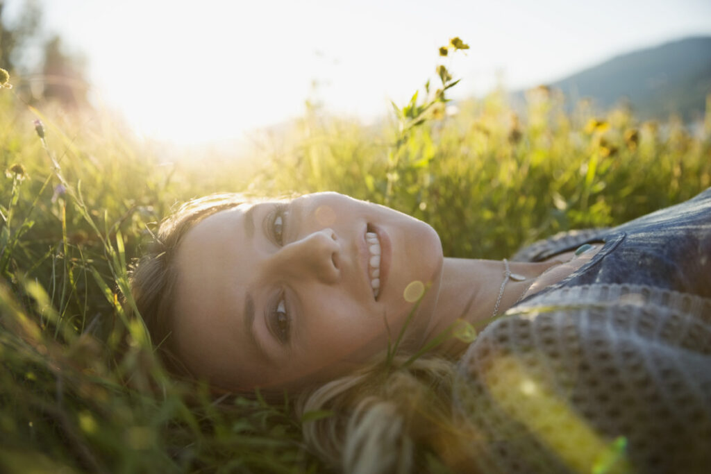 Portrait smiling young woman laying in sunny grass