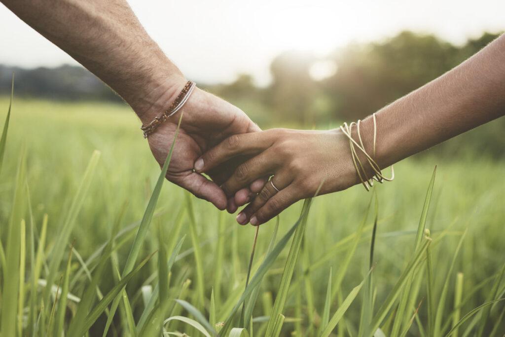Pärchen läuft Hände haltend durch Gras