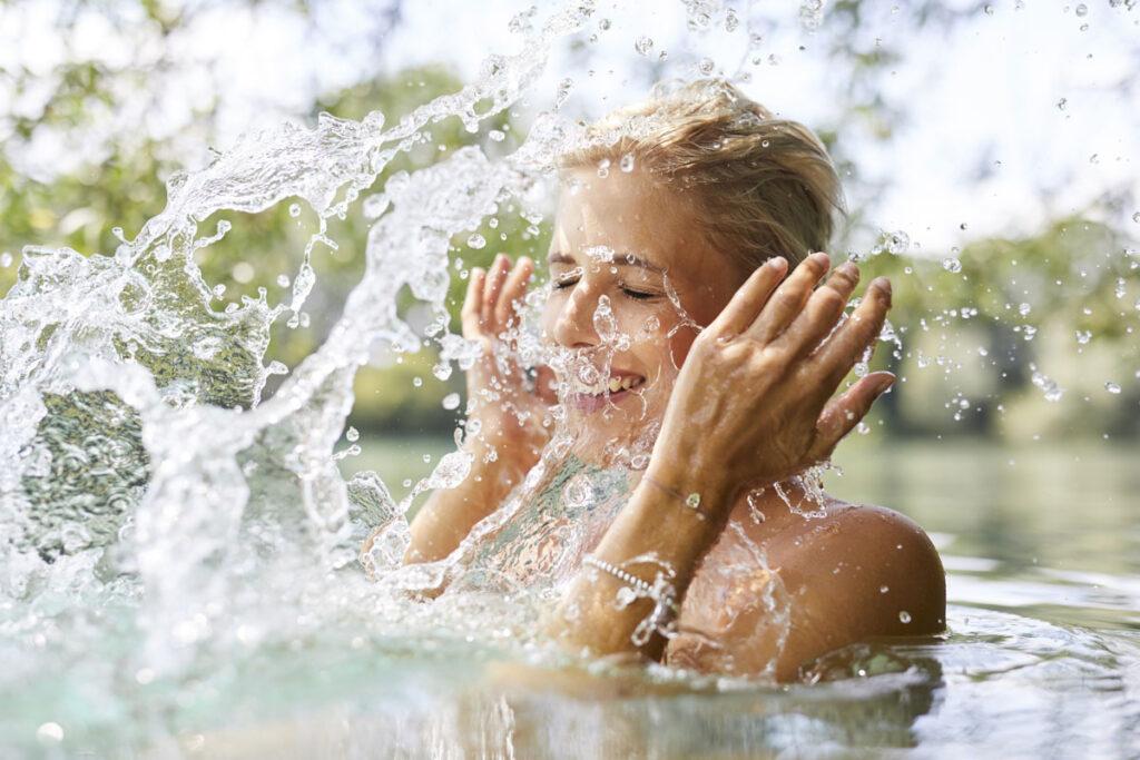 Frau spritzt sich Wasser ins Gesicht während dem baden
