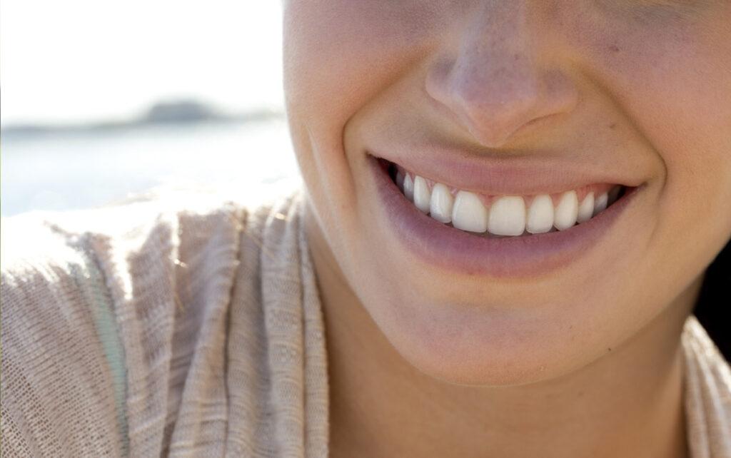 Frau mit strahlendem Lächeln an See